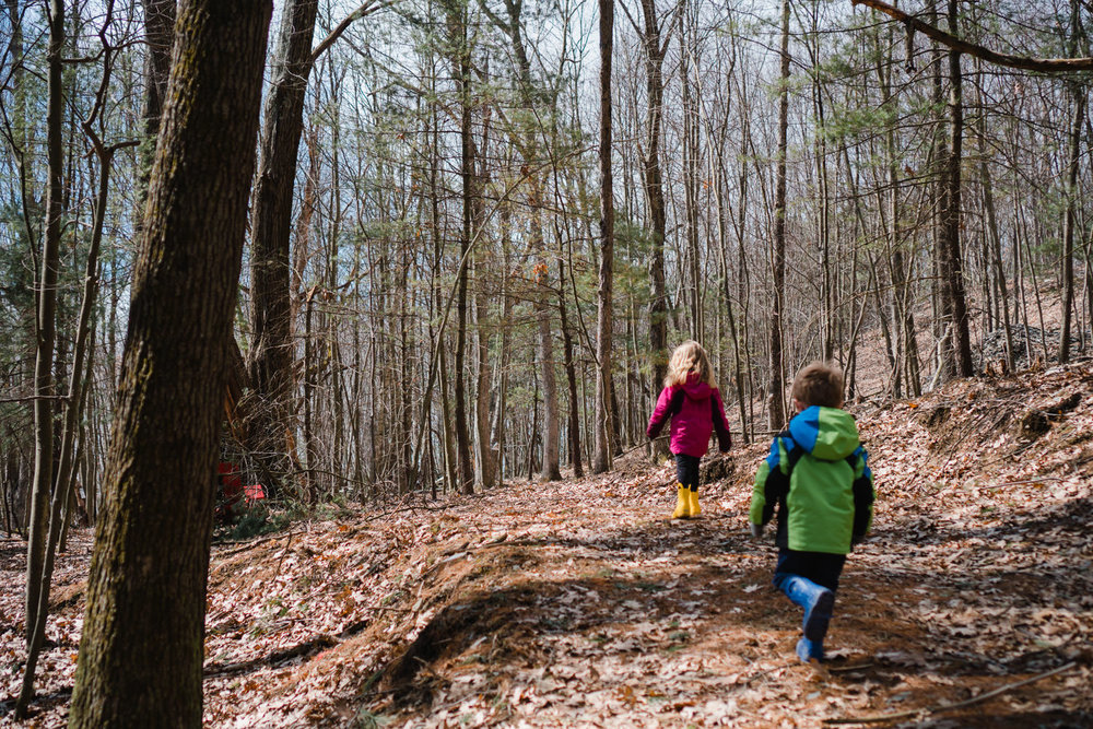 Two kids hike through a trail in the woods.