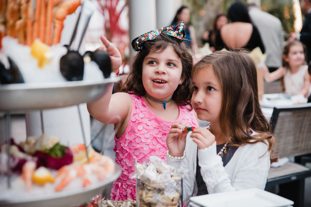Two little girls look at a seafood platter.