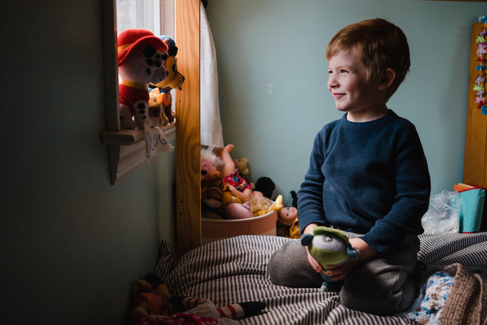 A little boy plays with toys on a window ledge.