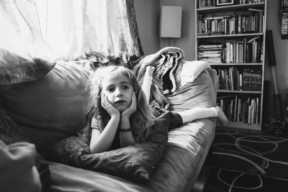 A little girl lies on a couch and watches TV.
