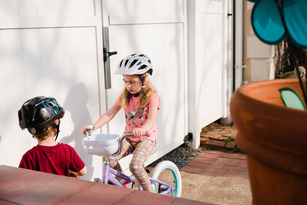 A little girl and boy ride bikes in a driveway.