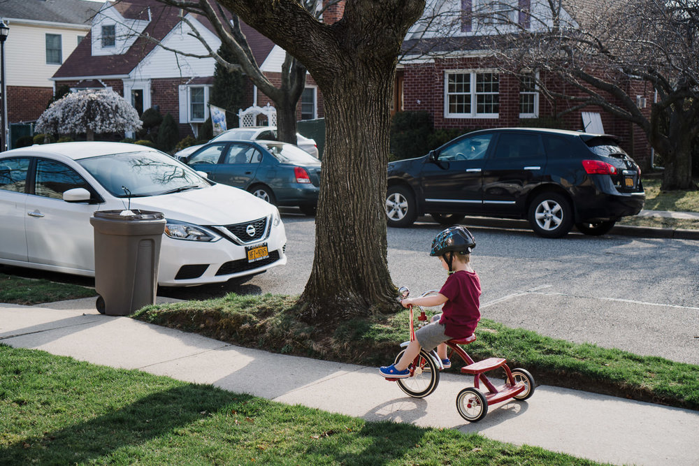 A little boy rides a tricycle down the sidewalk.