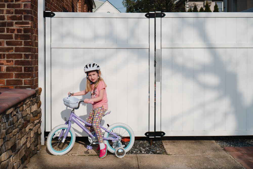 A girl rides her bike in a driveway.