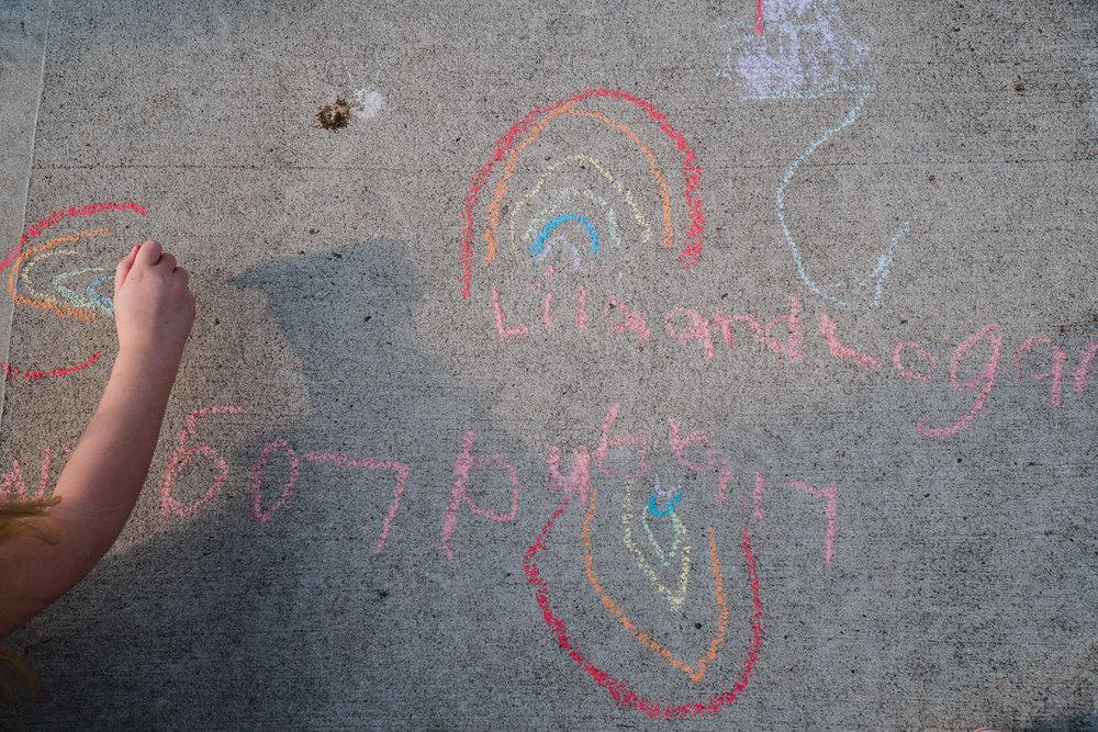 A child draws on the sidewalk with chalk.