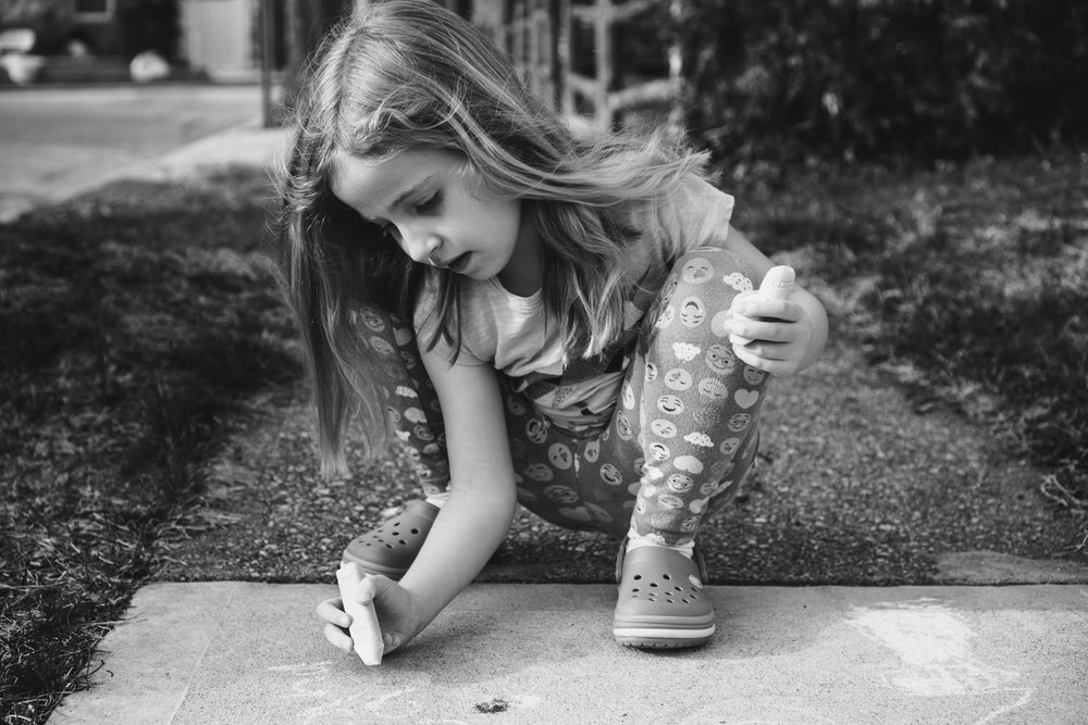 A little girl draws on the sidewalk with chalk.