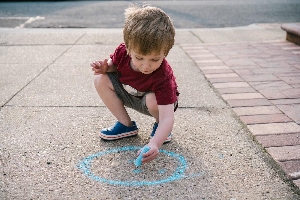 A little boy draws on the sidewalk with chalk.