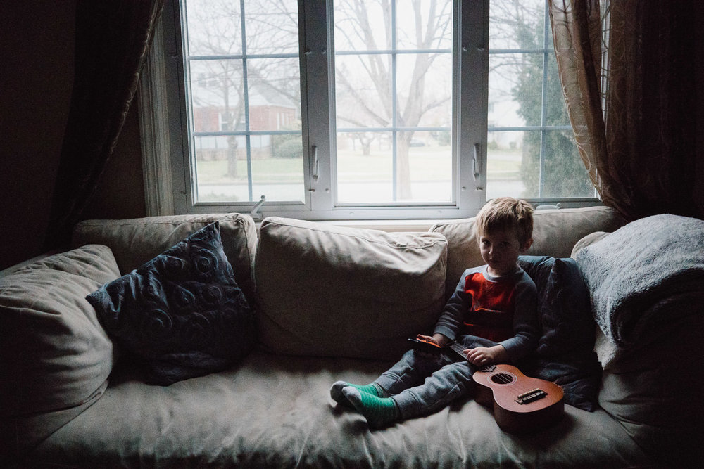 A little boy sits on a couch with a ukulele.