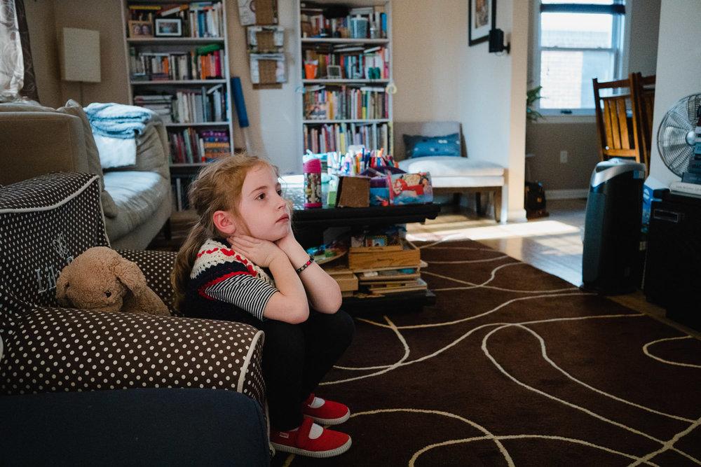 A little girl watches TV.