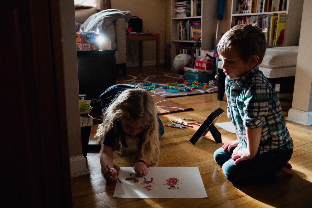 Two kids draw.
