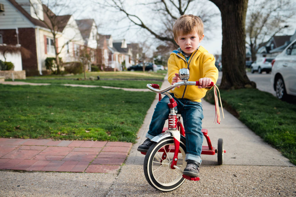 A little boy rides his tricycle.