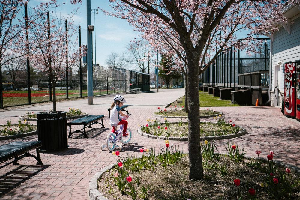 A little girl rides her bike through the Garden City Community Park.
