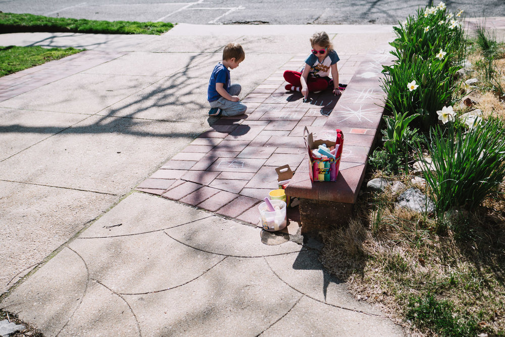 Two children draw in their driveway with chalk.