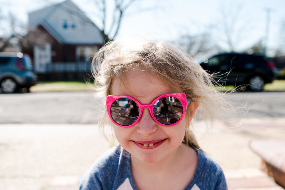 A little girl wears sunglasses and smiles at the camera.
