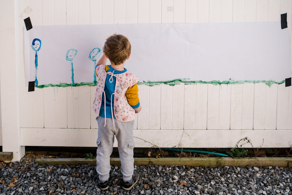 A little boy paints a big picture outside on a fence.