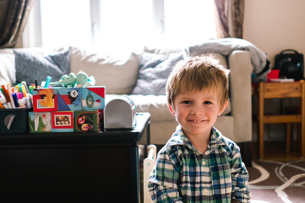A little boy smiles in his living room.