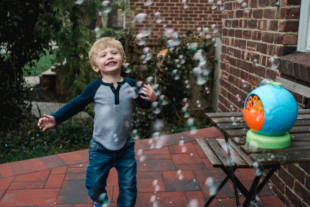 A little boy plays with a bubble machine.