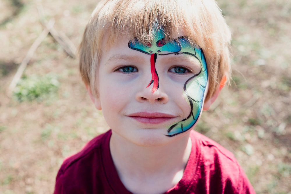 A little boy with snake face paint.