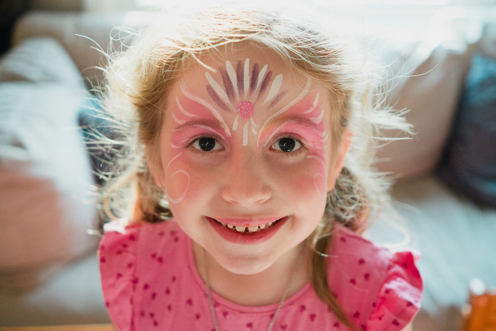 A little girl with pink face paint.