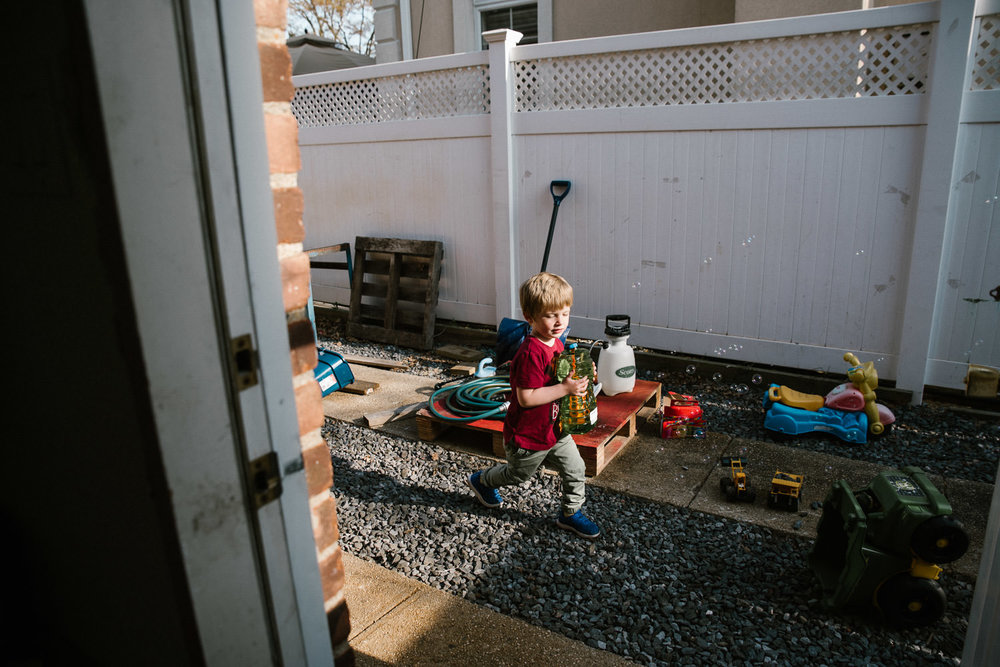 A little boy plays in a side yard.