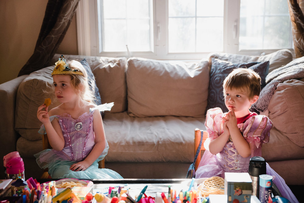 Two children dressed as princesses watch TV.