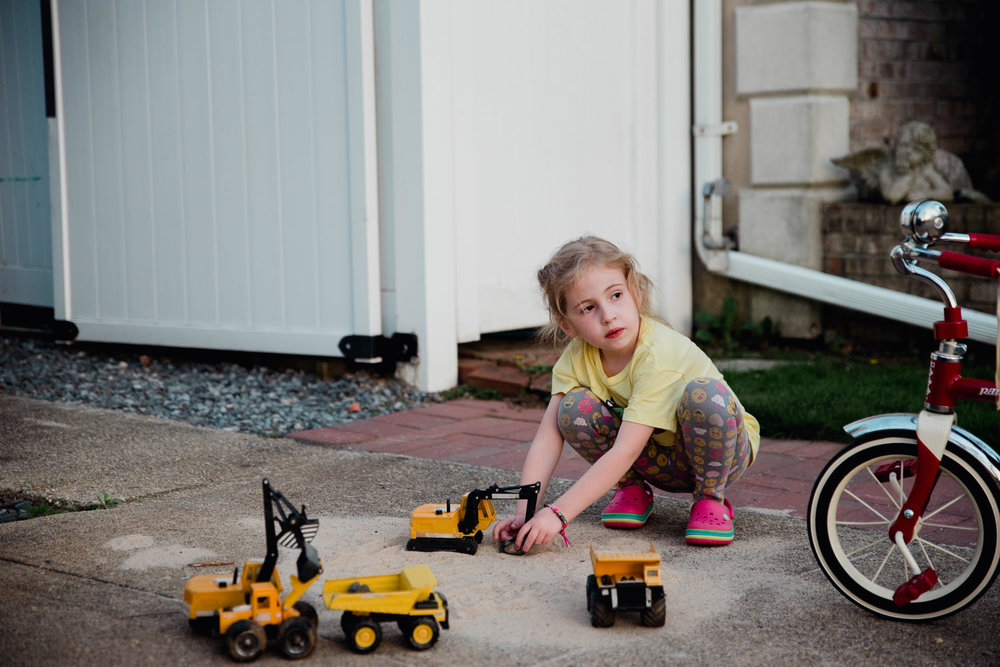 A little girl plays with trucks in some sand.