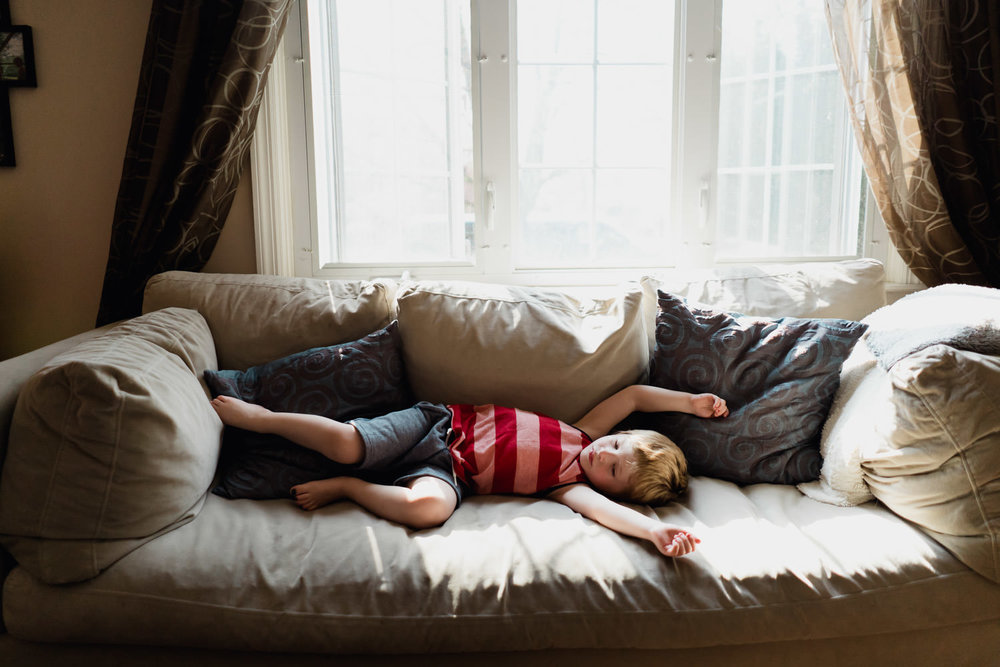 A little boy stretches on his couch.