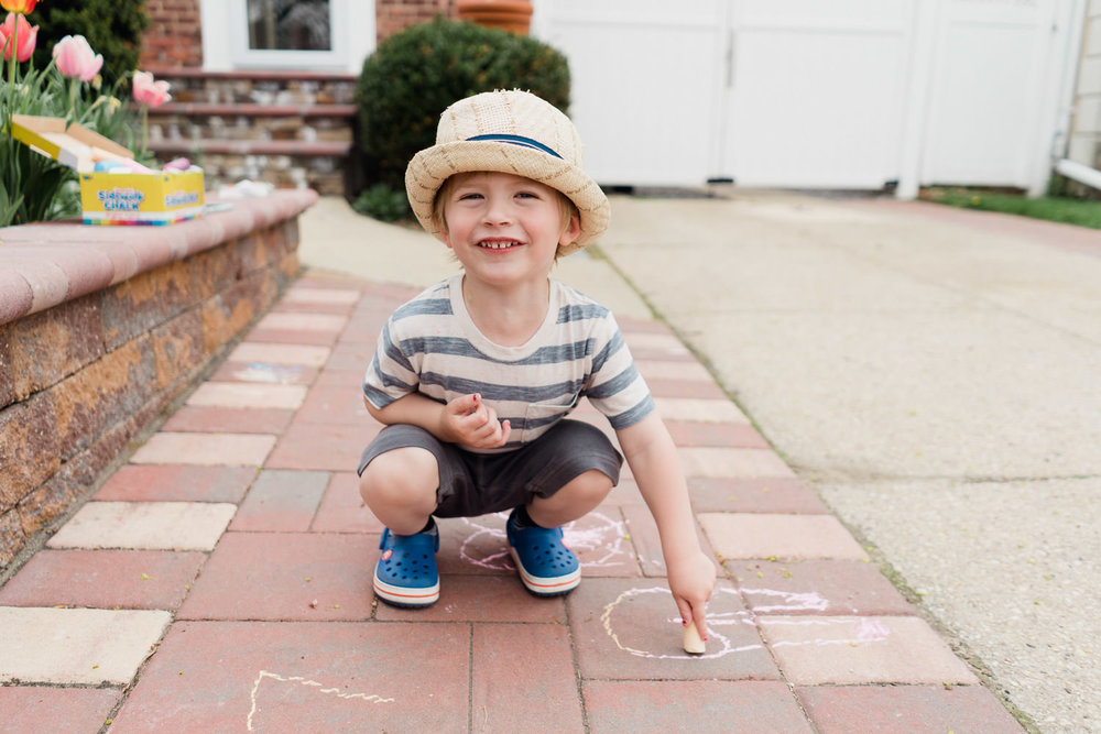 A little boy in a straw hat draws with chalk.