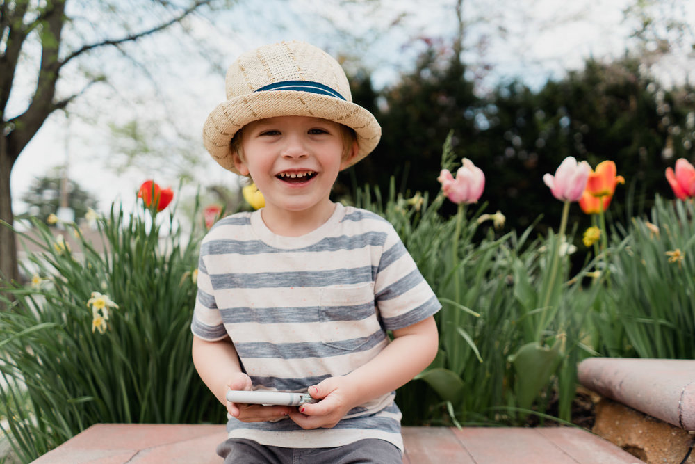 A little boy smiles in front of some tulips.