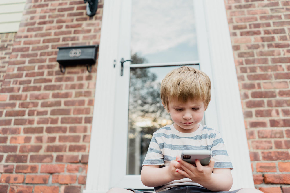 A little boy looks at a smartphone on a front porch.