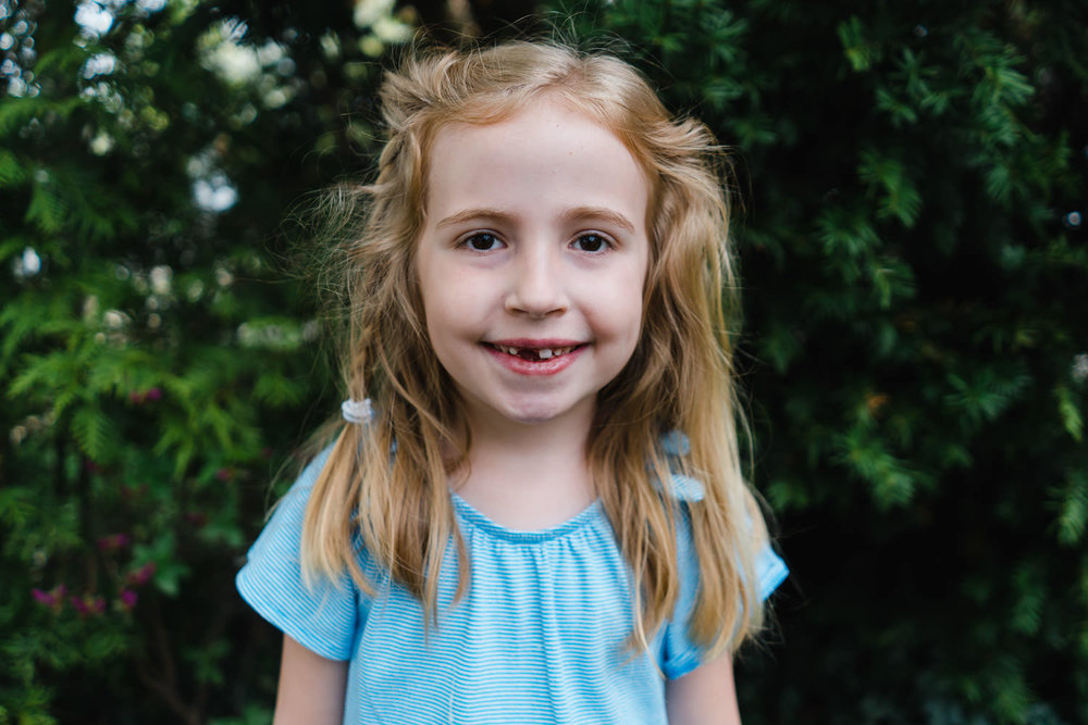 A little girl with a missing front tooth.