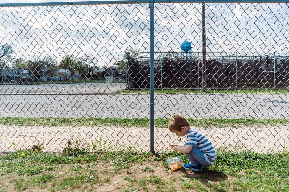 A little boy crouches down by a fence in Franklin Square.