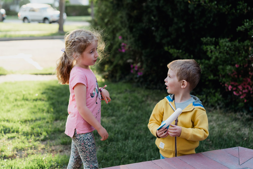 Two children play in their front yard.