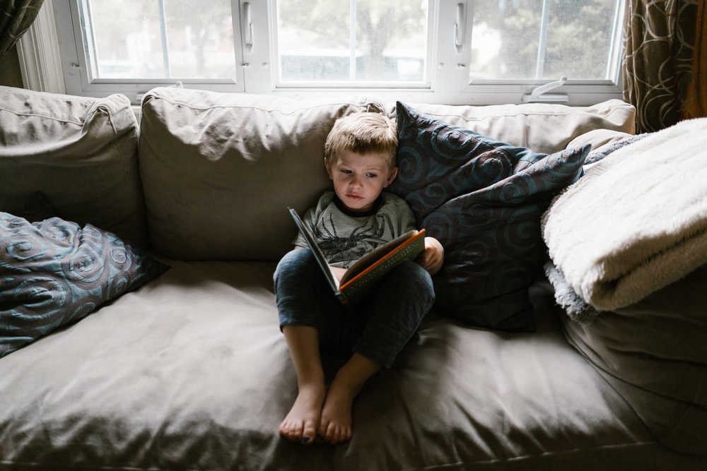 A little boy reads a book on a couch.