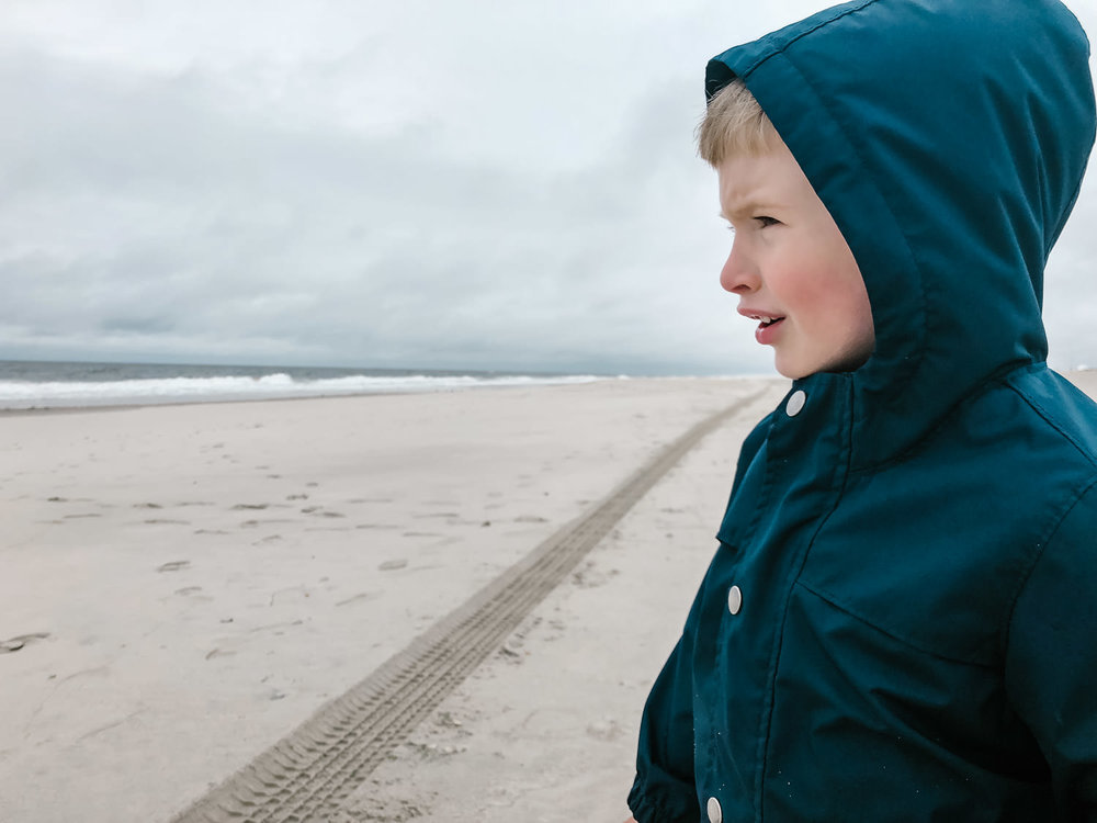 A little boy looks out at the ocean.