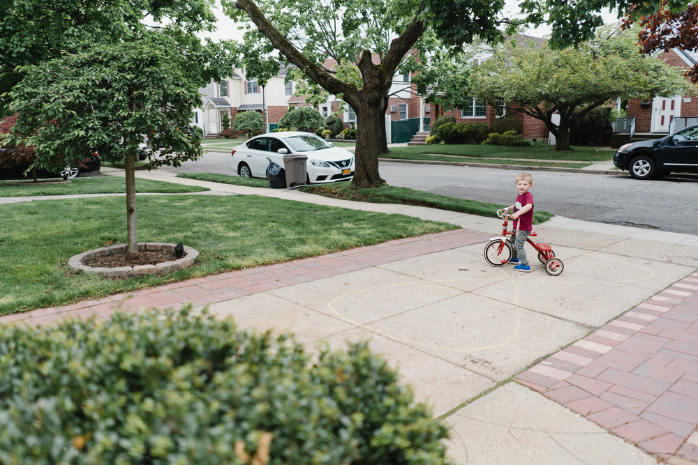 A little boy rides a trike in his driveway.