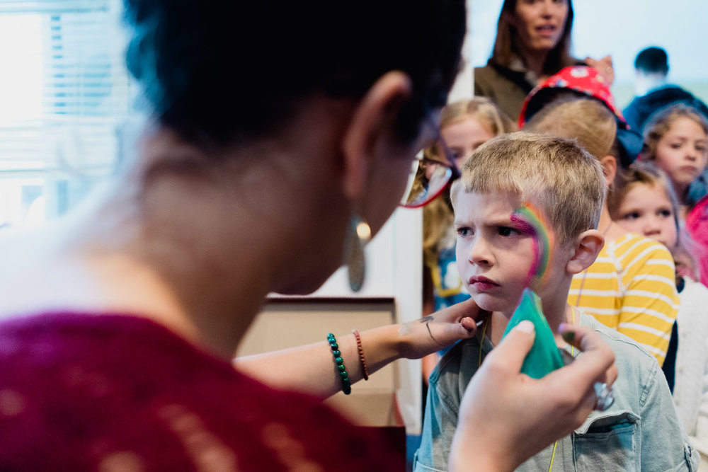 A little boy gets his face painted.