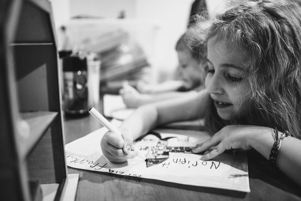 A little girl draws a picture.