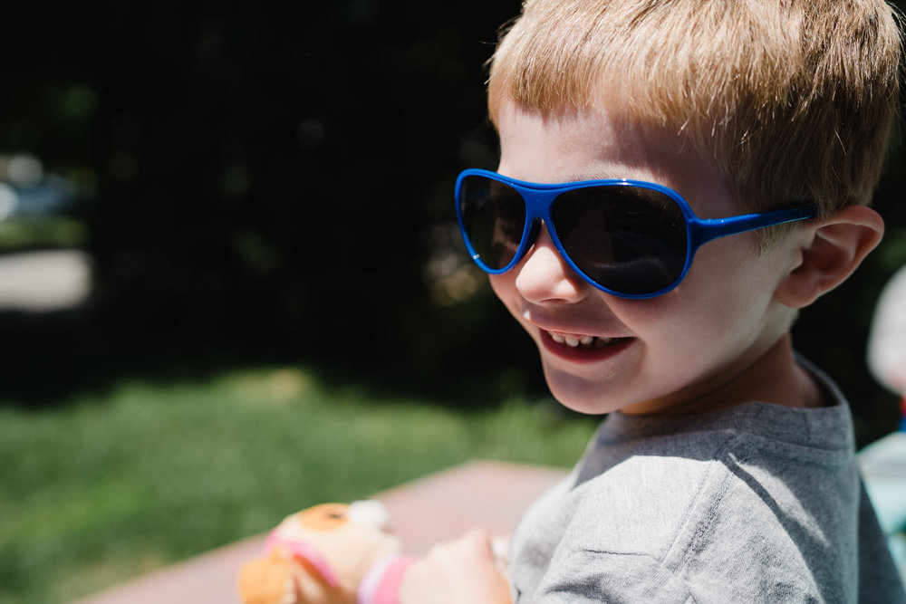 A little boy wears sunglasses.