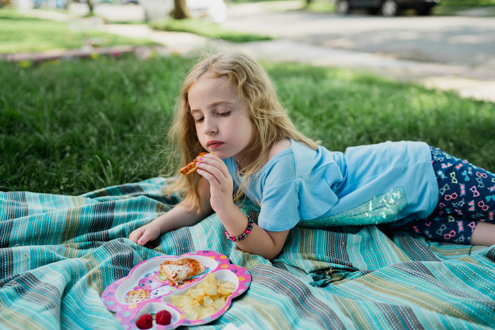 A little girl eats a picnic lunch on the lawn.