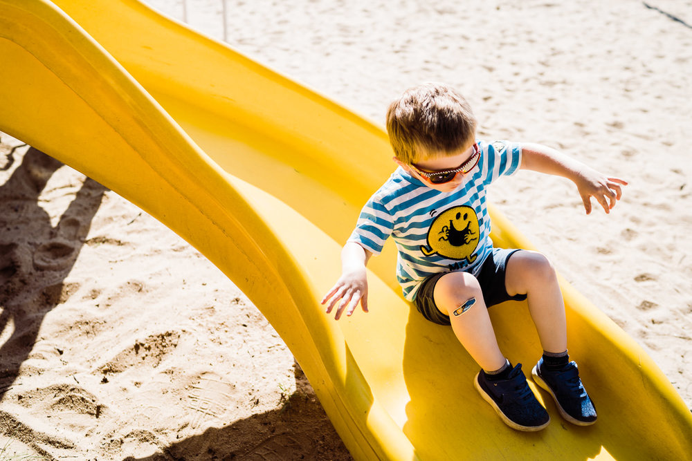 A little boy slides down a slide.