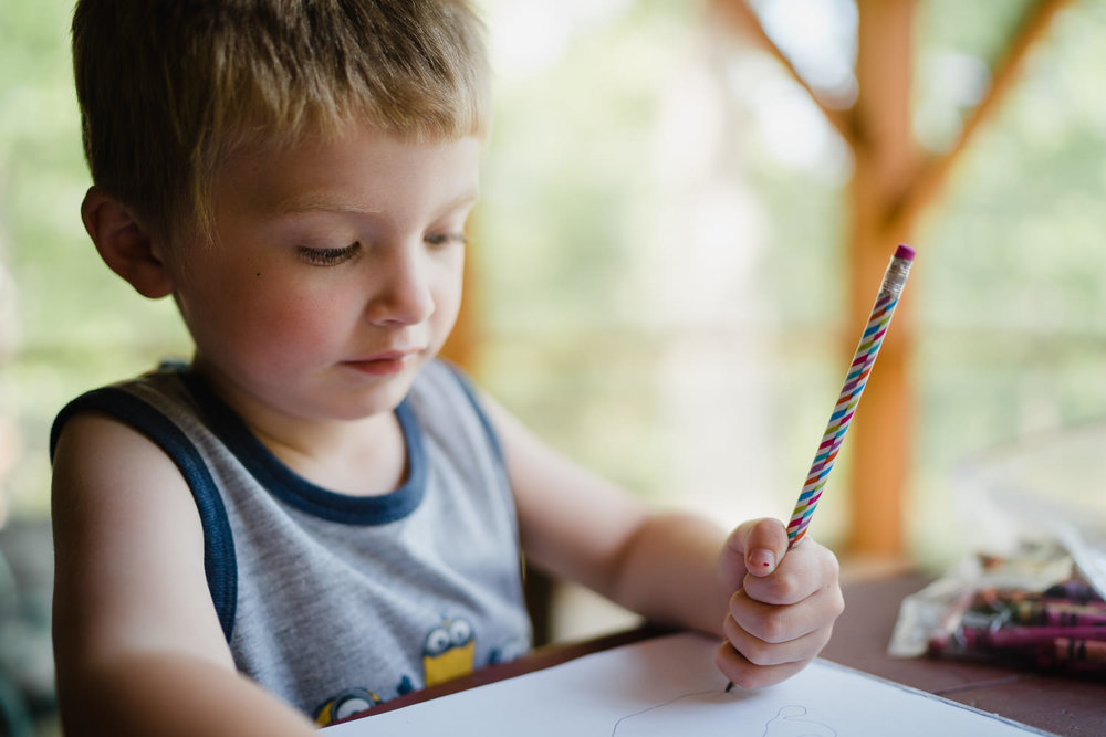 A little boy writes with a pencil at a picnic table.