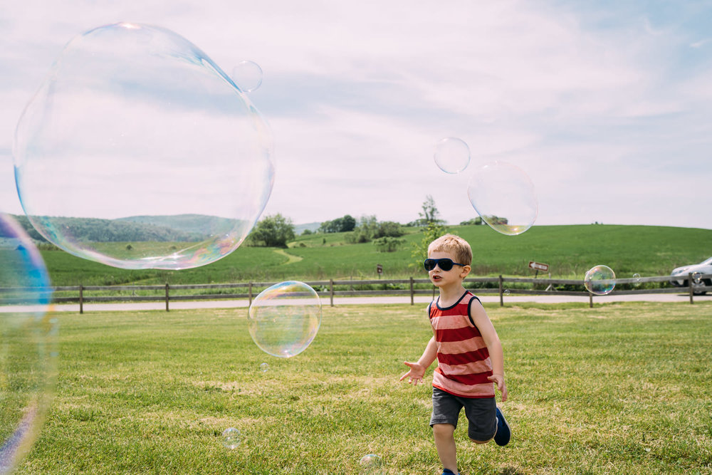 A little boy runs after bubbles at the Copake Farmer's Market.