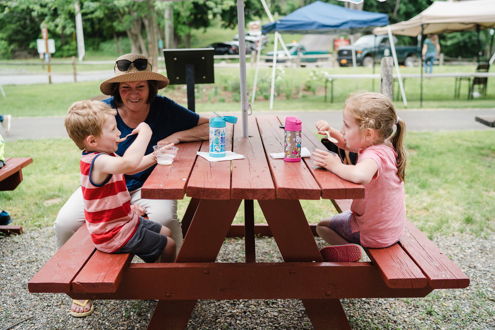 Children and their grandmother eat ice cream at a picnic table.