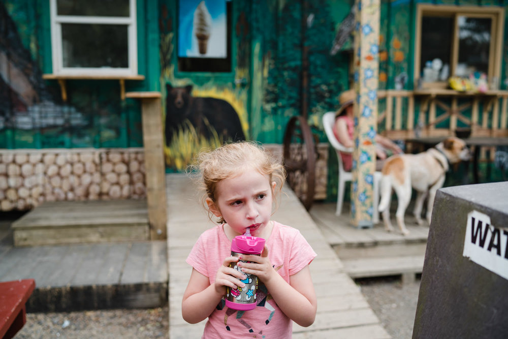 A little girl drinks some water outside a general store.