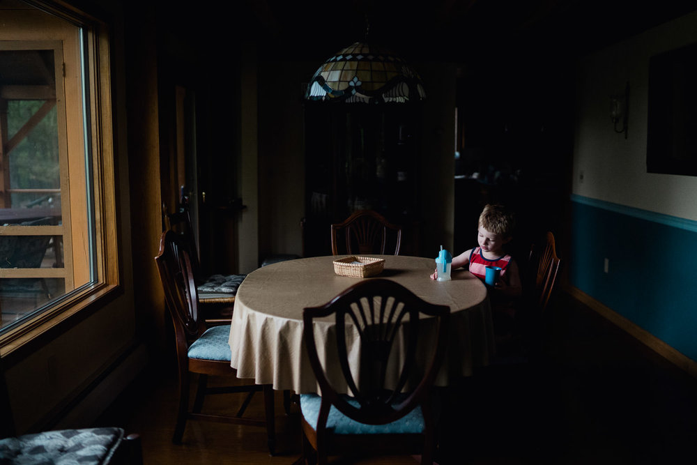 A little boy sits by himself at the dining table.