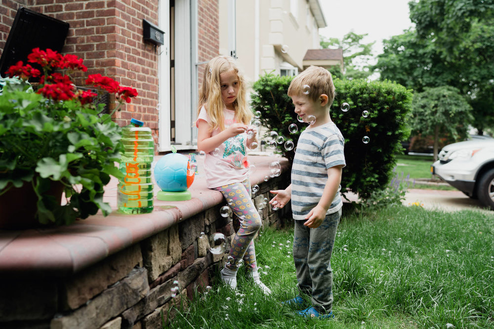 Two children play with bubbles in their front yard.