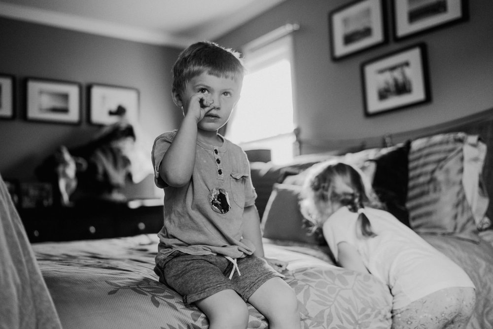 A little boy sits on his parents' bed and picks his nose.
