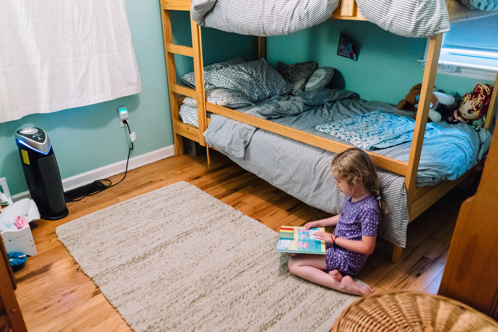 A little girl reads on the floor next to a bunkbed.