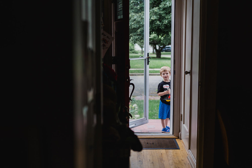 A little boy stands in the front doorway.