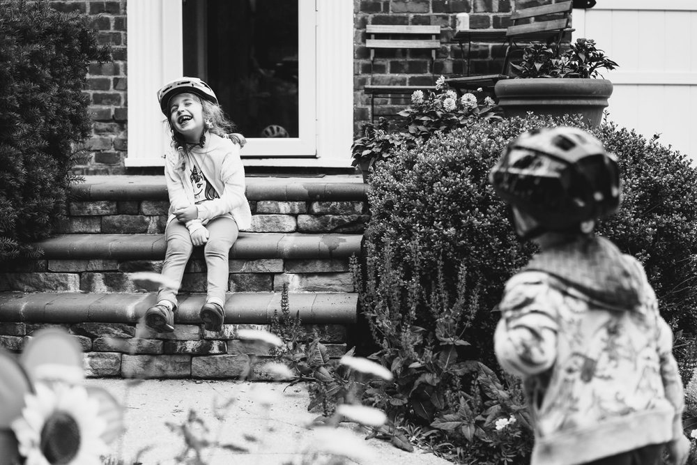 A little girl sits and laughs on her front steps.
